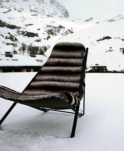 Structure en acier inox laqué noir brillant. Chaise longue en furrure écologique luxueuse et confortable. Adaptée à un usage extérieur pour les plus beaux chalets.