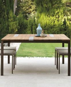 Garden table with stainless steel frame. Top in iroko wood and travertine. Patio furniture design by Ramon Esteve. Shop online for outdoor table and chairs.
