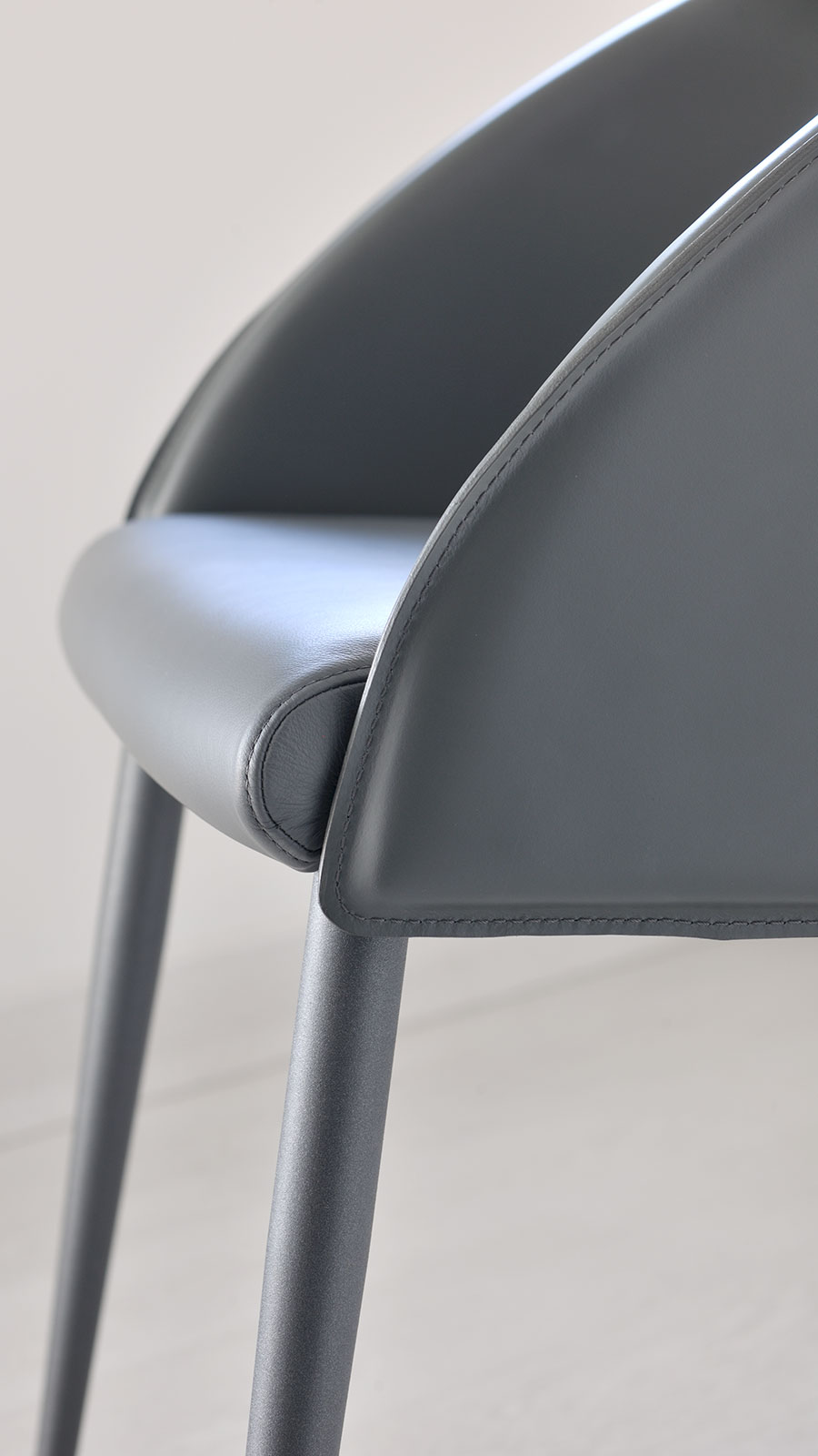 The double use of hide leather for its backrest and soft leather or eco-leather for its seat, create a unique padded armchair, modern and elegant.